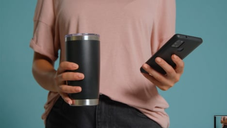 Close-Up-Shot-of-Young-Adult-Womans-Hands-Holding-Flask-and-Using-Smartphone-01