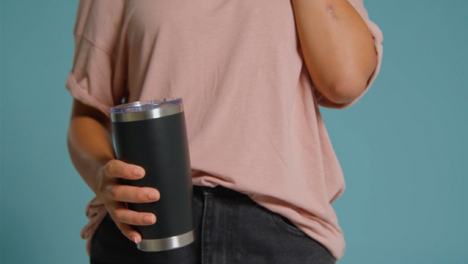 Close-Up-Shot-of-Young-Adult-Womans-Hands-Holding-Flask-and-Using-Smartphone-02