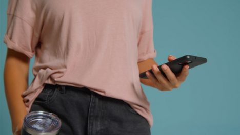 Close-Up-Shot-of-Young-Adult-Womans-Hands-Holding-Flask-and-Using-Smartphone-03