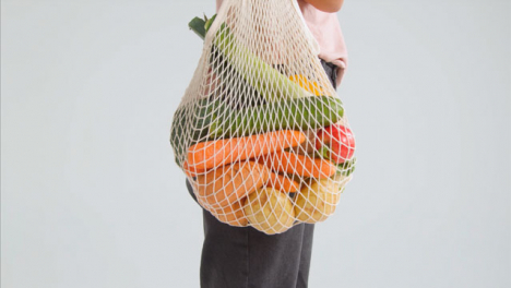 Side-Profile-Shot-of-Young-Adult-Woman-Holding-Bag-of-Vegetables