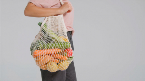 Tracking-Shot-of-Young-Adult-Woman-Holding-Bag-of-Vegetables-01