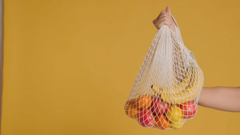 Medium-Shot-of-Young-Adult-Womans-Hand-Holding-Up-Bag-of-Fruit