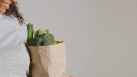 Side-Profile-Shot-of-Young-Adult-Woman-Holding-Brown-Paper-Bag-of-Vegetables
