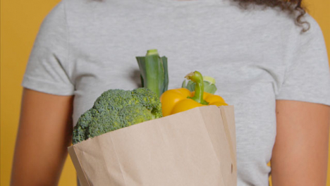 Close-Up-Shot-of-Young-Adult-Woman-with-Brown-Paper-Bag-of-Vegetables