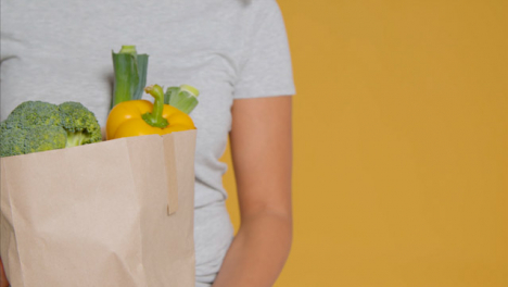 Sliding-Shot-of-Young-Adult-Woman-with-Brown-Paper-Bag-of-Vegetables-with-Copy-Space