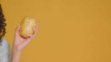 Close-Up-Shot-of-Young-Adult-Woman-Holding-Potato