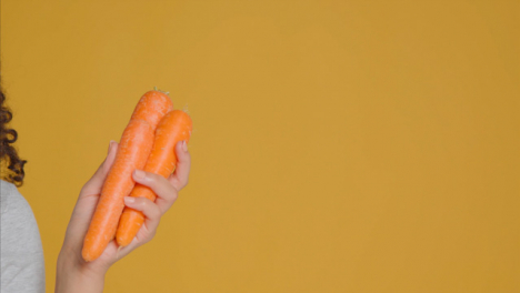 Close-Up-Shot-of-Young-Adult-Woman-Holding-Carrots