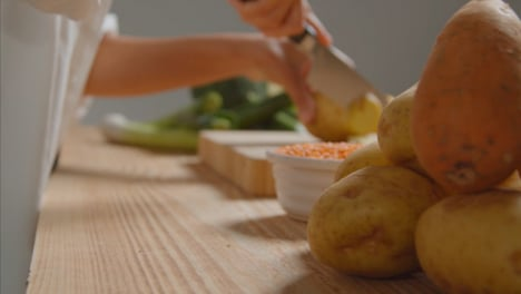 Tracking-Shot-of-Young-Adult-Woman-Slicing-Potato-04