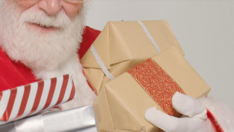 Close-Up-Shot-of-Santa-Holding-Some-Gifts-and-Presents