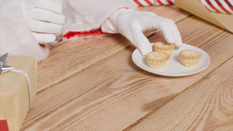 High-Angle-Shot-of-Santa-Picking-Up-Glass-of-Milk-and-Mince-Pie