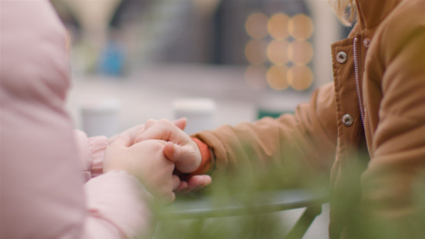 Close-Up-Shot-of-Two-Young-Women-Holding-Hands-at-Outdoor-Table