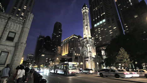 Chicago-busses-pass-water-tower-at-night