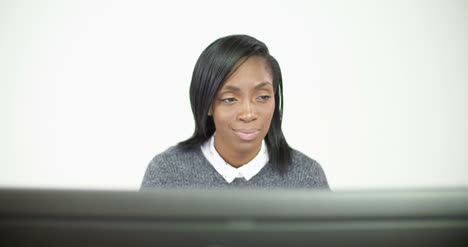 Woman-Working-at-Computer-and-Smiling