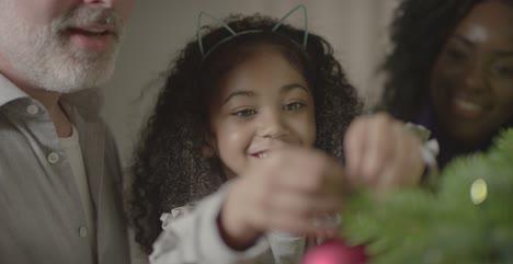 Child-Placing-Decoration-on-Christmas-Tree-1