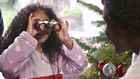 Girl-Unwrapping-Binoculars-at-Christmas