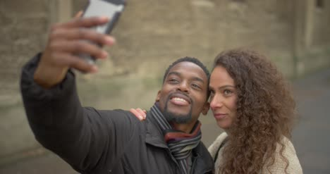 Woman-Kisses-Man-on-Cheek-for-Selfie