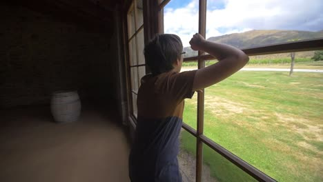 Boy-Looking-Out-of-Barn-Window-