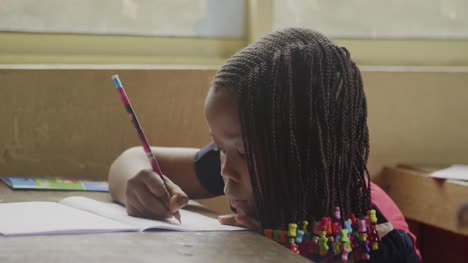 Young-African-Girl-Writing-in-Classroom