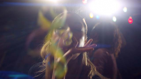 Mujer-joven-sopla-streamer-a-la-cámara