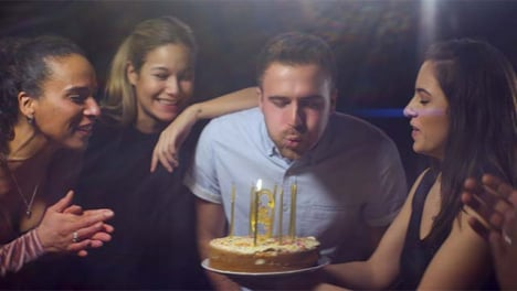 Man-Blows-Out-Birthday-Cake-Candles-with-Friends