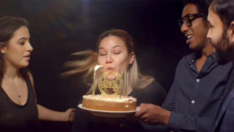 Woman-Blows-Out-Birthday-Cake-Candles