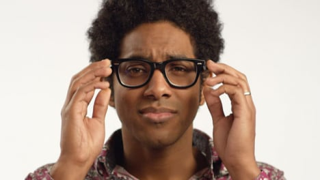 Close-up-Young-Man-Puts-Glasses-on