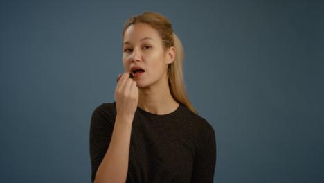 Woman-Applies-Lipstick-Facing-Camera