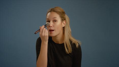 Young-Woman-Applies-Blusher-Facing-Camera
