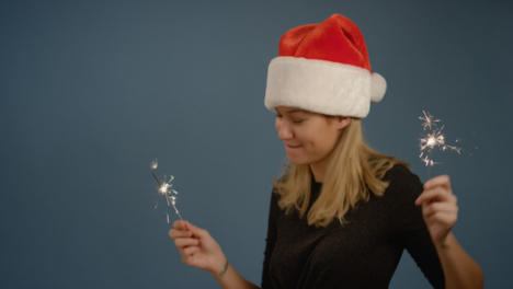 Dancing-Woman-wearing-Santa-Hat-with-Sparklers