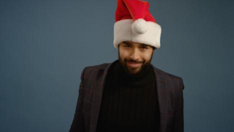 Man-Puts-on-Santa-Hat-and-Smiles-at-Camera