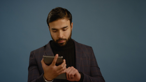 Young-Man-Browses-Tablet