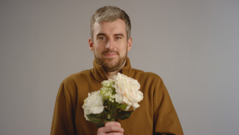 Man-Holds-Flowers-Towards-Camera