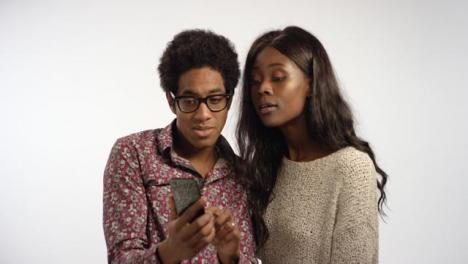 Smiling-Couple-Look-at-Photos-on-Teléfono