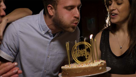 Young-Man-Blows-Out-Birthday-Cake-Candles