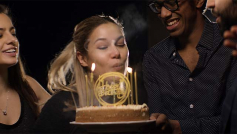 Young-Woman-Blows-Out-Birthday-Cake-Candles