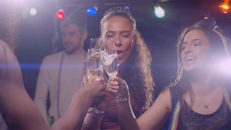 Las-mujeres-jóvenes-bailan-y-hacen-clic-en-sus-bebidas