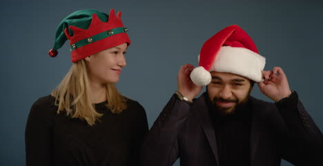 Woman-Flicks-Santa-Hat-on-Man
