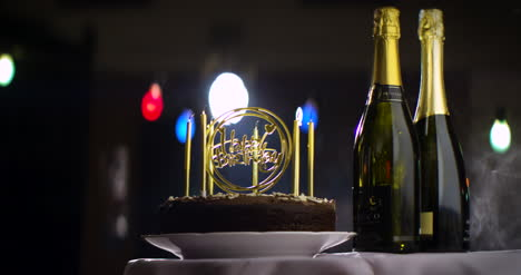 Birthday-Cake-With-Candles-Blown-Out-On-Table-