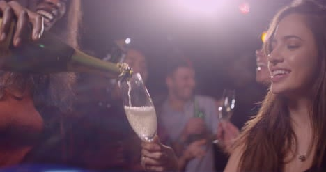 Young-Woman-Pours-Champagne-at-Party