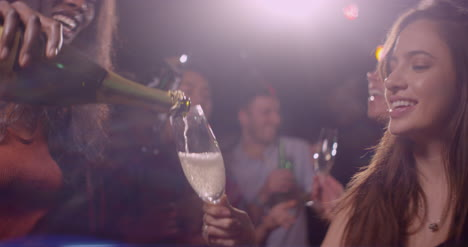 Mujer-joven-vierte-champán-en-fiesta