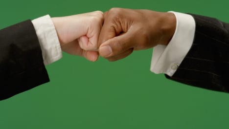 CU-Colleagues-in-suits-fist-bump-on-green-screen