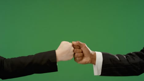 CU-Colleagues-in-suits-fist-bump-explosion-on-green-screen