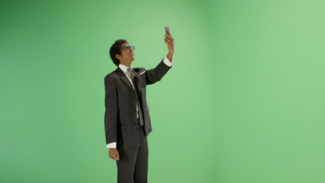 Annoyed-man-trying-find-phone-signal-on-green-screen