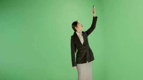 Businesswoman-trying-find-phone-signal-on-green-screen