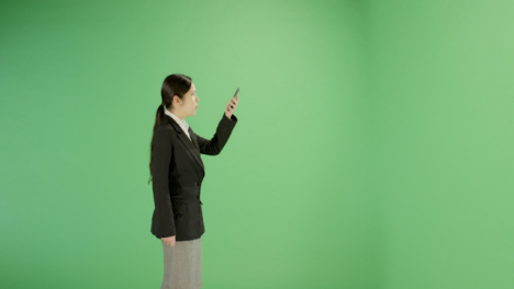 Businesswoman-looking-for-phone-signal-on-green-screen