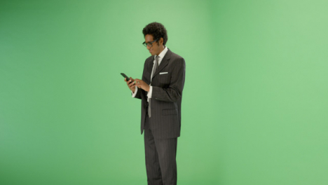 Businessman-texting-on-phone-with-green-screen