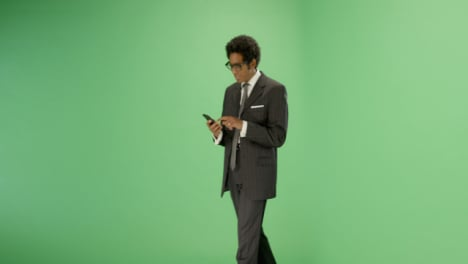 Empresario-enviando-mensajes-de-texto-mientras-camina-en-la-pantalla-verde