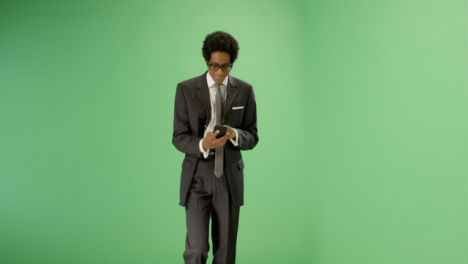 Texting-Businessman-walking-towards-camera-on-green-screen