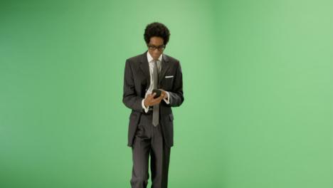 Texting-Businessman-walking-towards-camera-on-green-screen