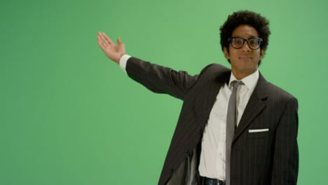 Businessman-gestures-with-one-arm-on-green-screen